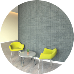 A wall covered in Ricochet®  Flexible Wall Protection with 2 lime green chairs with a small grey table between them