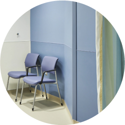 A doctor's office with 2 blue chairs next to a wall