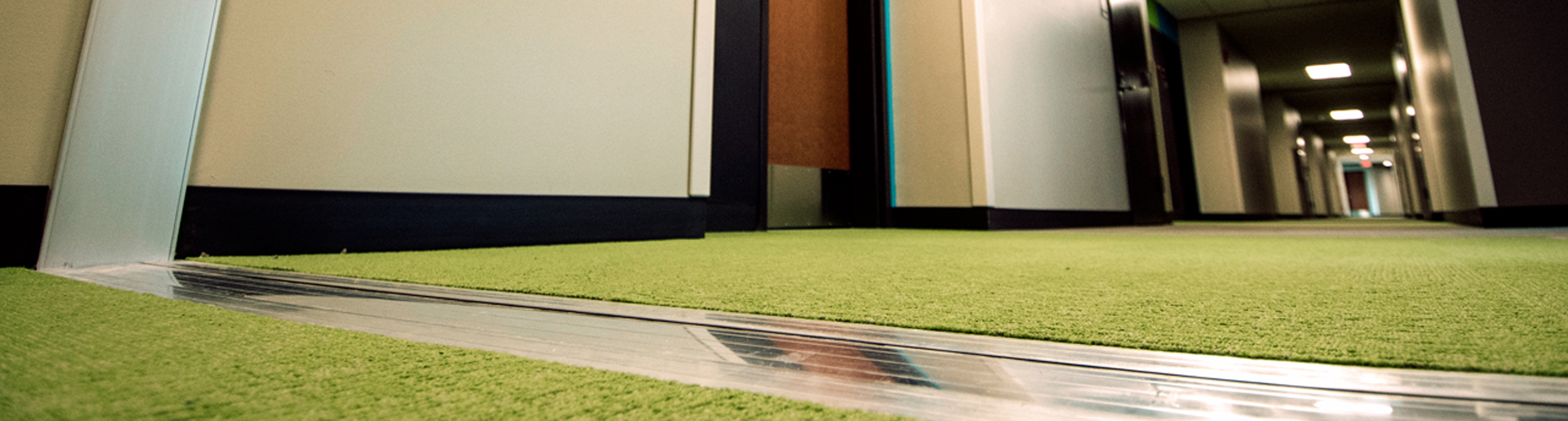 Floor expansion joint running up a wall and through green carpet