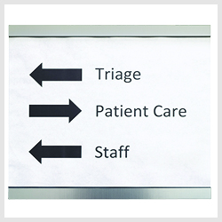 A directional sign with arrows showing the way to Triage, Patient Care, and Staff