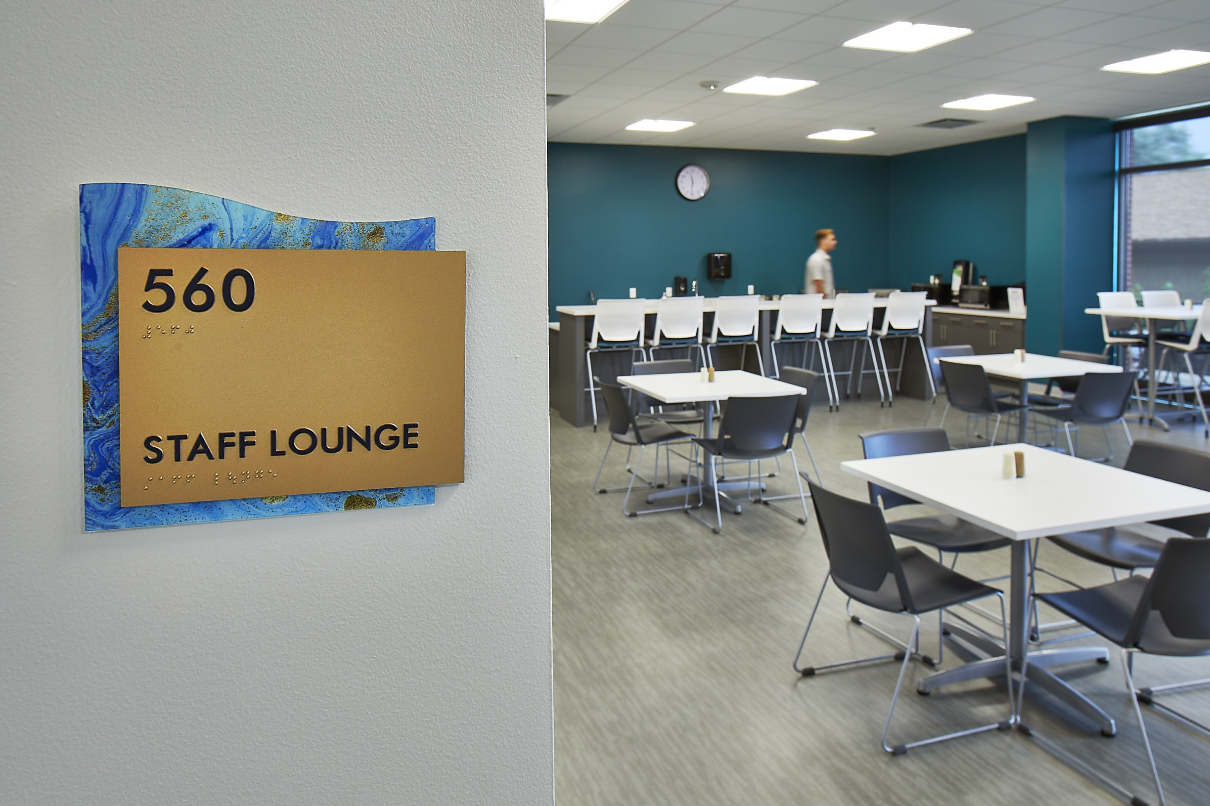 Staff Lounge Sign with blue and gold backing  on a wall next to a lounge with tables