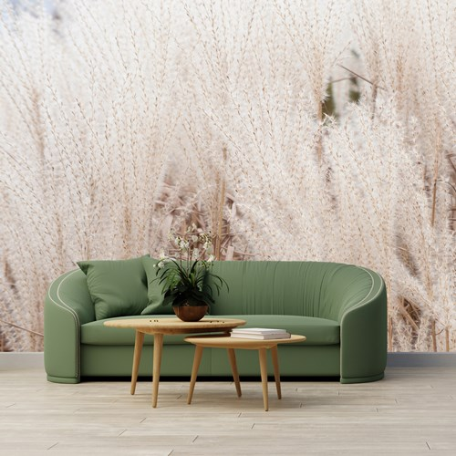 A green couch with a small table in front.  Behind the couch is a decorative wall.