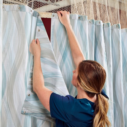 Woman showing how to use the snaps to change cubicle curtains